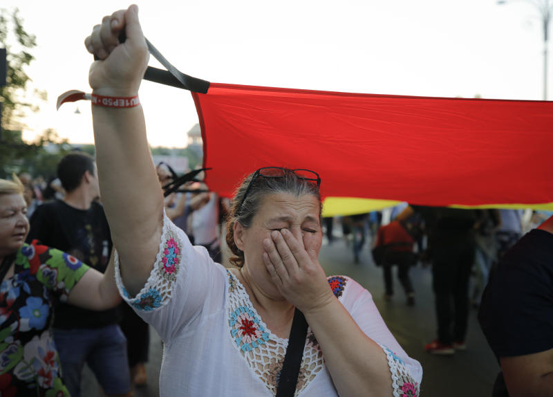 A woman cries holding a large Romanian flag as she take part in a march from the government headquarters in memory of a 15 year-old girl, raped and killed in southern Romania, after police took 19 hours from the moment she called the country's emergency hotline to intervene, in Bucharest, Romania, Saturday, July 27, 2019. Thousands of people took part Saturday evening in Bucharest in a march protesting the handling of the case, blaming Romanian officials for negligence, incompetence and a lack of empathy. (AP Photo/Vadim Ghirda)