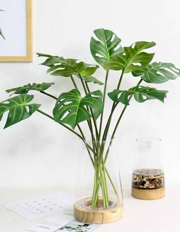 "For anyone who dreams of turning their space into a jungle but can't keep a fern alive to save their life, this bunch of faux monstera leaves will bring a tropical flair without the hassle. $13, Etsy. <a href=""https://www.etsy.com/listing/692631794/12pcs-artificial-monstera-palm-tree"" rel=""nofollow noopener"" target=""_blank"" data-ylk=""slk:Get it now!"" class=""link rapid-noclick-resp"">Get it now!</a>"