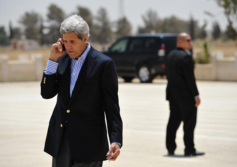 U.S. Secretary of State John Kerry speaks on the phone, before boarding a helicopter to Amman, at Mafraq air base after visiting the Zaatari refugee camp in Mafraq, Jordan, Thursday, July 18, 2013. Angry Syrian refugees urged Kerry on Thursday to do more to help opponents of President Bashar Assad's government, venting frustration at perceived inaction on their behalf. (AP Photo/Mandel Ngan, Pool)
