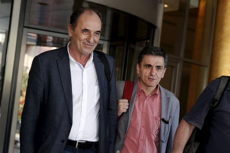 Greek Economy Minister Stathakis and Finance Minister Tsakalotos leave a hotel following an overnight meeting in Athens