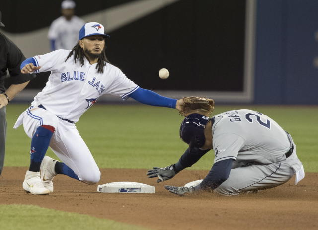 Tampa Bay Rays' Avisail Garcia advances to second base on a throwing error as Toronto Blue Jays' Freddy Galvis can't handle the throw in the seventh inning of a baseball game in Toronto on Saturday, April 13, 2019. (Fred Thornhill/The Canadian Press via AP)