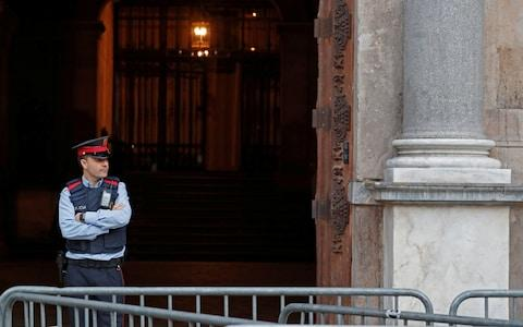 A Mossos d'Esquadra, a Catalan regional police officer, stands guard outside the Generalitat Palace, the Catalan regional government headquarter in Barcelona - Credit: YVES HERMAN/REUTERS