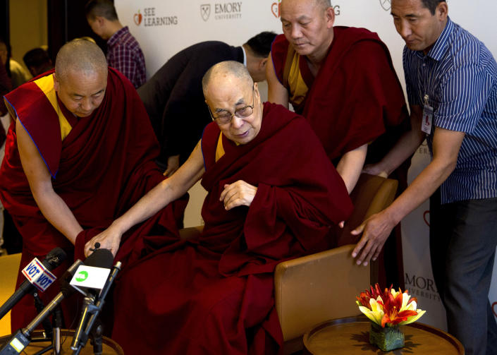 FILE - In this April 4, 2019, file photo, Tibetan spiritual leader the Dalai Lama, center, is assisted by his aides as he arrives to interact with an audience of educators, in New Delhi, India. The Dalai Lama has been hospitalised in the Indian capital with chest infection and is feeling much better. The Tibetan spiritual leader's spokesman Tenzin Taklha says the Dalai Lama is under medication and likely to spend a day or two in the hospital. The Dalai Lama flew to New Delhi from Dharmsala for consultations with doctors and was hospitaliszd on Tuesday, April 9, 2019. (AP Photo/Manish Swarup, File)