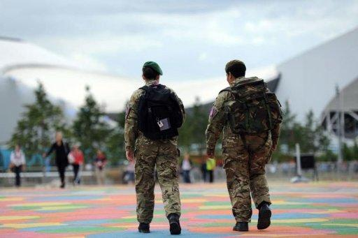 Soldiers walk in front of the Aquatic Centre in the Olympic Park in east London