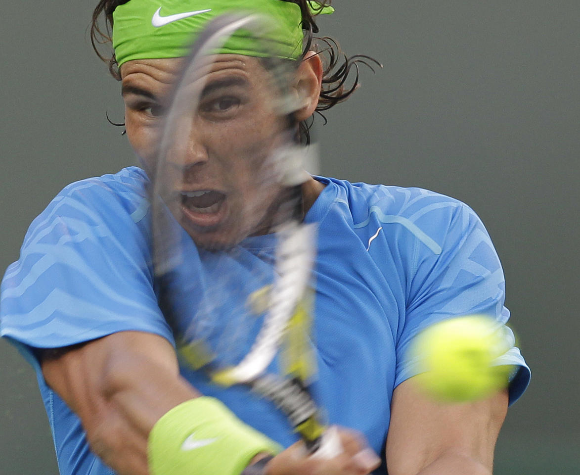 Rafael Nadal, of Spain, returns a shot to David Nalbandian, of Argentina, during a match at the BNP Paribas Open tennis tournament Friday, March 16, 2012, in Indian Wells, Calif. Nadal won the match 4-6, 7-5, 6-4. (AP Photo/Darron Cummings)