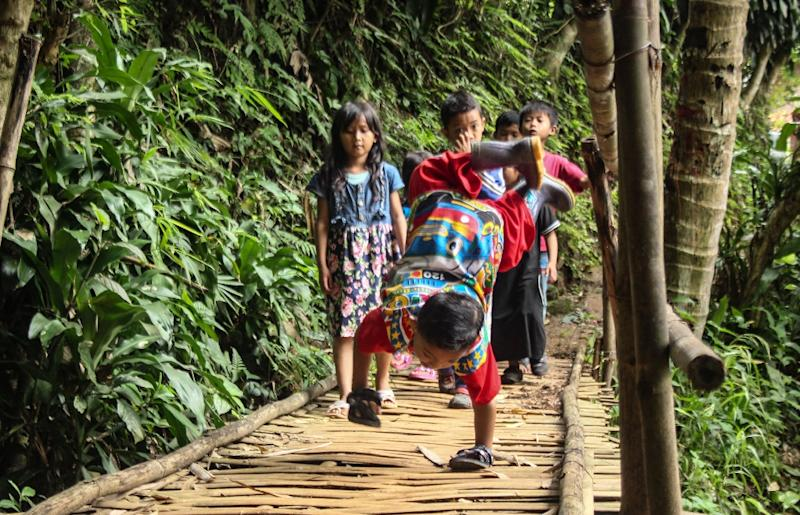 Holik crawls from his West Java village across rocky paths and an old wooden bridge that he navigates on his hands alone, as his sneakers dangle in the air (AFP Photo/CANTIGIE NUR FERDINAND)