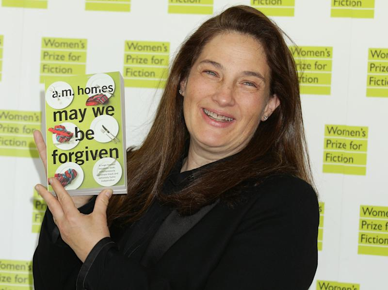 "American novelist A.M. Homes holds a copy of her book 'May We Be Forgiven' at the Royal Festival Hall, London Wednesday June 5, 2013. Homes has won this year's Women's Prize for Fiction Wednesday with her sixth novel ""May We Be Forgiven."" Homes beat award winning writer Hilary Mantel and three other finalists for the 30,000-pound ($45,000) prize _ previously known as the Orange Prize, one of Britain's most prestigious literary awards. (AP Photo/ Yui Mok/PA) UNITED KINGDOM OUT"