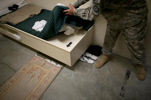 GUANTANAMO BAY, CUBA - JUNE 25: (EDITORS NOTE: Image has been reviewed by the U.S. Military prior to transmission.) An arrow marks the direction for prayer in a static display setup for visitors in a prison cell at camp 6 where prisoners are housed in the communal facility at the U.S. military prison for 'enemy combatants' on June 25, 2013 in Guantanamo Bay, Cuba. President Barack Obama has recently spoken again about closing the prison which has been used to hold prisoners from the invasion of Afghanistan and the war on terror since early 2002. (Photo by Joe Raedle/Getty Images)