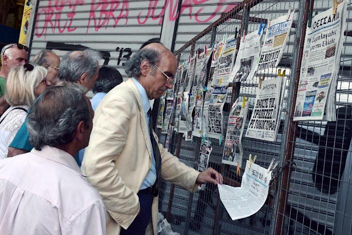 People read newspapers' headlines in central Athens, on June 29, 2015 (AFP Photo/Louisa Gouliamaki)