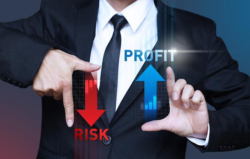 """A man in a suit holding his hands out, framing the words """"RISK"""" with an arrow pointing down and """"PROFIT"""" with an arrow pointing up"""