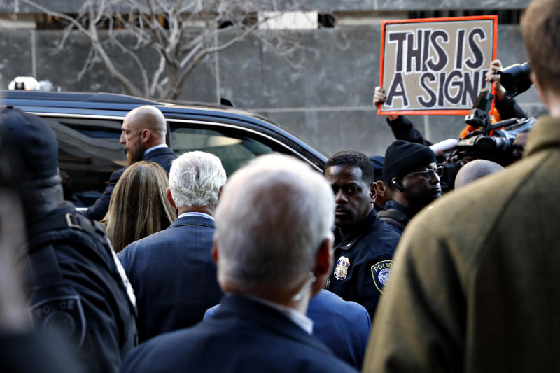 Former campaign adviser for President Donald Trump, Roger Stone, center left, walks to his vehicle as he leaves federal court Thursday, Feb. 21, 2019, in Washington, between members of the media, security, and protesters. A judge has imposed a full gag order on Trump confidant Roger Stone after he posted a photo on Instagram of the judge with what appeared to be crosshairs of a gun. (AP Photo/Jacquelyn Martin)