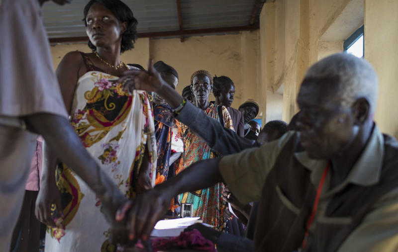 Voters wait in line to cast their vote, as others have their fingers dipped in ink to show they have done so, in an abandoned school used as a polling center in the disputed border region of Abyei, whose ownership is claimed by both Sudan and South Sudan, Sunday, Oct. 27, 2013. Hundreds of people in the disputed border region of Abyei voted Sunday in a referendum that they hope will decide whether they join Sudan or South Sudan, a local leader said, but the exercise lacked the official backing of either of the two governments. (AP Photo/Mackenzie Knowles-Coursin)