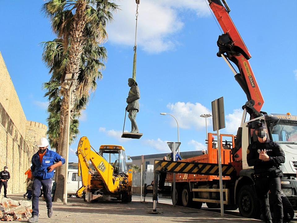 A crane removes the statue of Franco located in front of the wall of Melilla's old town (Europa Press via Getty Images)