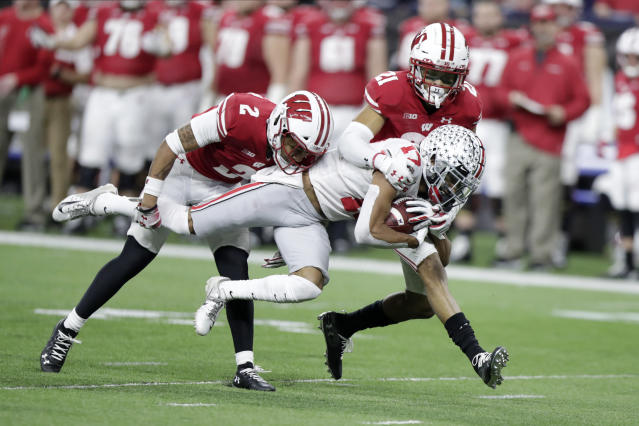 Ohio State wide receiver Chris Olave (17) is tackled by Wisconsin safety Reggie Pearson (2) and cornerback Caesar Williams (21) during the second half of the Big Ten championship NCAA college football game Saturday, Dec. 7, 2019, in Indianapolis. (AP Photo/Michael Conroy)