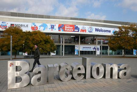 FILE PHOTO: Man walks past sculpture in front of entrance of Mobile World Congress in Barcelona