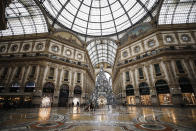 The almost deserted Galleria Vittorio Emanuele II shopping arcade, in Milan, Italy, Thursday, Dec. 24, 2020. Italy went into a modified nationwide lockdown Thursday for the Christmas and New Year period, with restrictions on personal movement and commercial activity similar to the 10 weeks of hard lockdown Italy imposed from March to May when the country became the epicenter of the outbreak in Europe. (AP Photo/Luca Bruno)