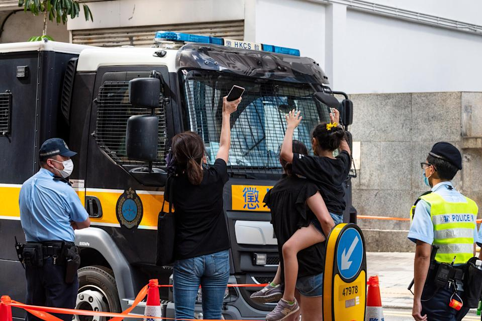 <p>Relatives wave to Correction Services Department van thought to be carrying Jimmy Lai and other prominent activists</p> (EPA)