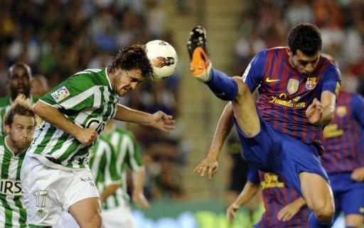 Barcelona's Sergio Busquets (R) fights for the ball with Real Betis' Javier Chica