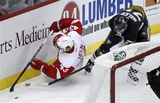 Pittsburgh Penguins' Evgeni Malkin (71) tries for the puck as Detroit Red Wings' Darren Helm (43) falls along the boards in the first period of the NHL hockey game on Tuesday, Dec. 13, 2011, in Pittsburgh. (AP Photo/Keith Srakocic)