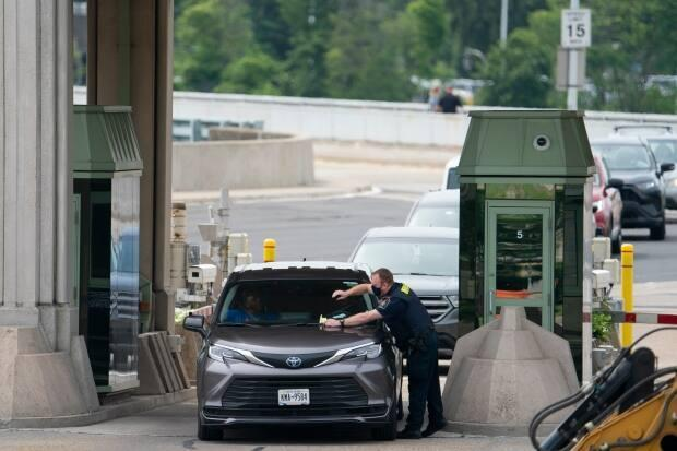 A CBSA officer places a document on the windshield of a car entering Canada and asks it to pull off to the side in Niagara Falls, Ontario on Friday, July 16, 2021. (Peter Power/The Canadian Press - image credit)