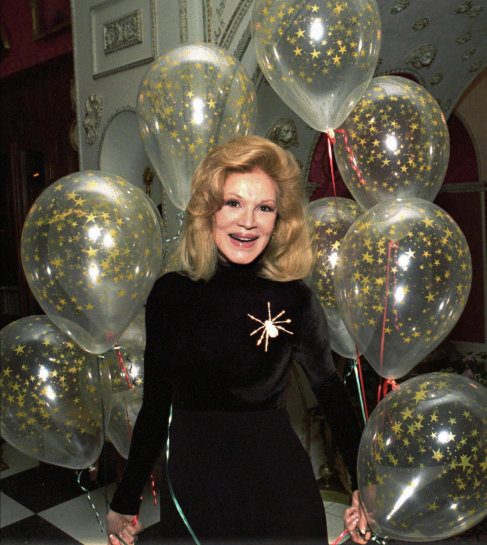 FILE - In this Tuesday, Dec. 12, l995. file photo, Phyllis McGuire, the youngest of The McGuire Sisters, smiles after receiving a cluster of balloons from longtime friends Debbie Reynolds and Rip Taylor at her home in Las Vegas. Phyllis McGuire, the last surviving member of the three singing McGuire Sisters who topped the charts with several hits in the 1950s, has died, Tuesday, Dec. 31, 2020 (AP Photo/Lennox McLendon, File)
