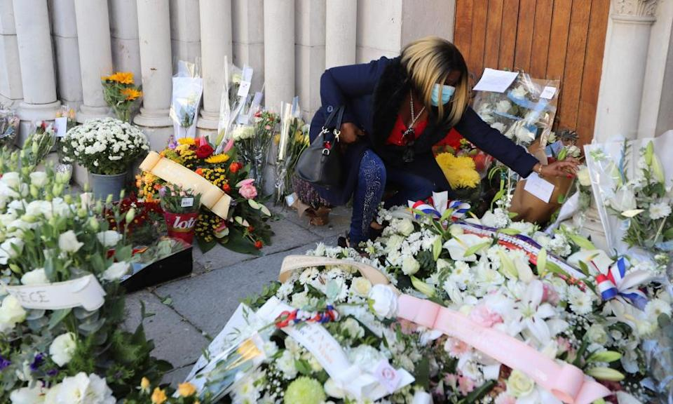 A woman lays flowers in front of the Notre-Dame de l'Assomption Basilica in Nice.