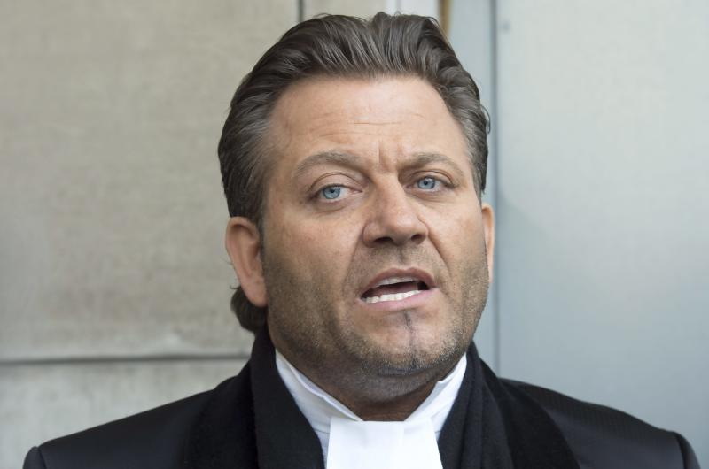 """FILE - In this March 17, 2017 file photo, Amedeo Dicarlo, lawyer for Karim Baratov, is photographed outside court in Hamilton, Ontario, Canada. Dicarlo said Wednesday, April 5, he has taken steps to ensure his client won't flee if he's released on bail. Officials allege that Baratov poses an """"extremely high flight risk'' because of his alleged ties to Russian agents. (Frank Gunn/The Canadian Press via AP)"""