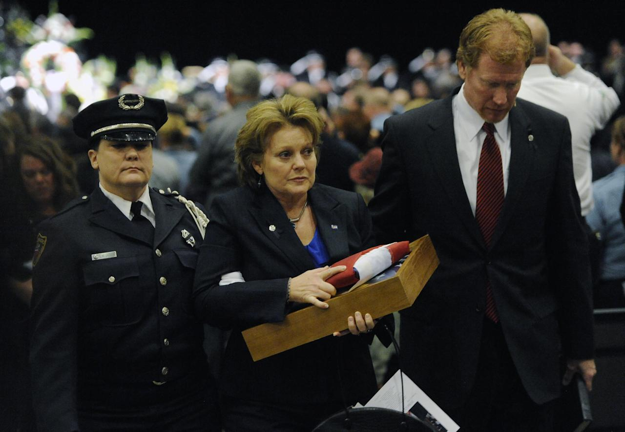 Lisa Clements, the wife of Tom Clements, exits from his memorial service with their minister, Pastor Matt Heard, right, and L.M. Jaros, left, during the public memorial for the chief executive of the Department of Corrections held at New Life Church in Colorado Springs, Colo., on Monday, March 25, 2013. Tom Clements was shot and killed when he opened the front door of his home last week in Monument, Colo. (AP Photo/The Gazette, Jerilee Bennett, Pool)