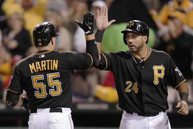 Pittsburgh Pirates' Russell Martin (55) is greeted by teammate Pedro Alvarez who was on base for his two-run home run off Cincinnati Reds starting pitcher Homer Bailey (34) during the second inning of a baseball game in Pittsburgh Saturday, Sept. 21, 2013. (AP Photo/Gene J. Puskar)