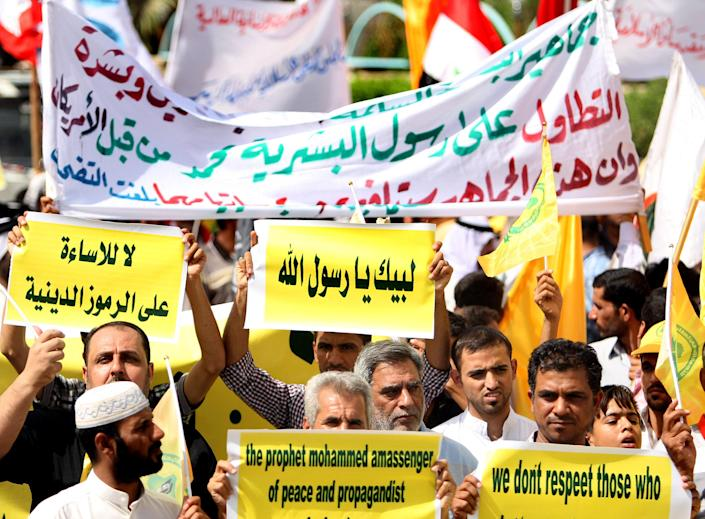 "Iraqis chant slogans during a protest in Basra, 340 miles (547 kilometers) southeast of Baghdad, Iraq, Friday, Sept. 14, 2012. In Basra, about 1,000 Iraqis marched the streets and burned the American and Israeli flags. ""Freedom doesn't mean offending two billion Muslims,"" one banner said. (AP Photo/Nabil al-Jurani)"