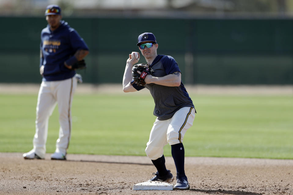 Milwaukee Brewers infielder Brock Holt throws to first as shortstop Orlando Arcia looks on, left, during spring training baseball Wednesday, Feb. 19, 2020, in Phoenix. Holt and the Brewers finalized a one-year contract Wednesday, a deal that includes a team option for 2021. (AP Photo/Gregory Bull)