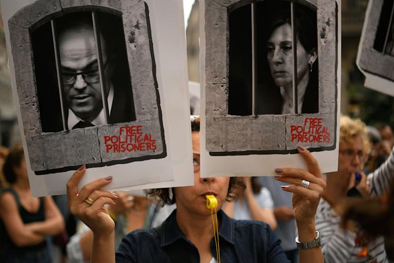 A woman holds placards depicting pictures of jailed Catalan separatist leaders Jordi Turull and Carme Forcadell in Barcelona after the ruling: AFP via Getty Images