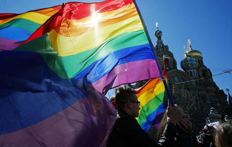"""FILE - In this Wednesday, May 1, 2013, file photo, gay rights activists carry rainbow flags as they march during a May Day rally in St. Petersburg, Russia. When the Sochi Winter Olympics begin on Friday, Feb. 7, 2014 many will be watching to see whether Russia will enforce its law banning gay """"propaganda"""" among minors if athletes, fans or activists wave rainbow flags or speak out in protest. The message so far has been confusing. (AP Photo/Dmitry Lovetsky, File)"""