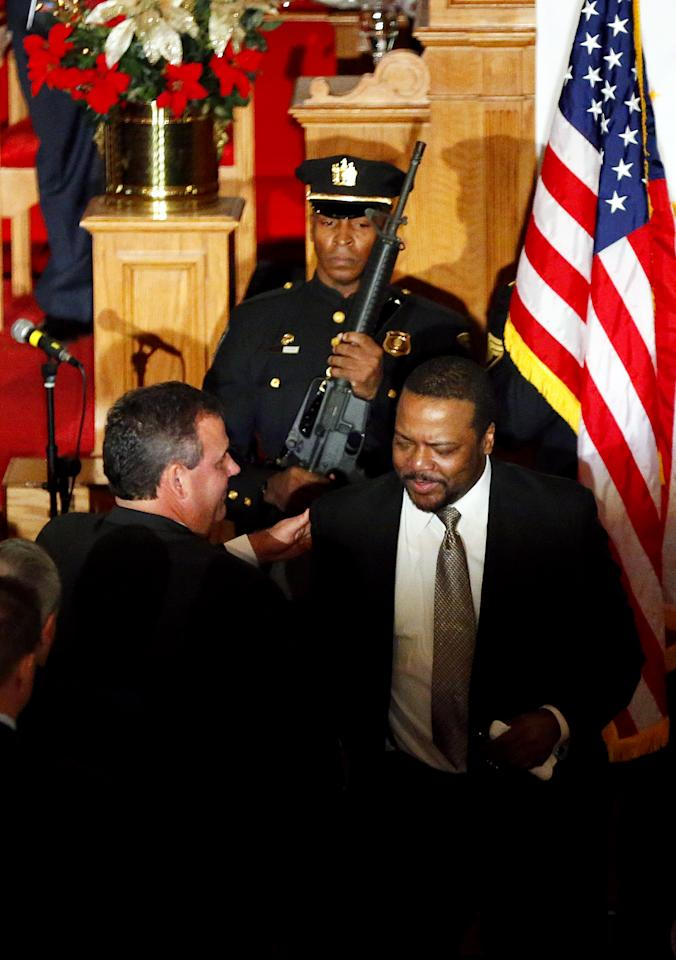 New Jersey Gov. Chris Christie shakes hugs Pastor Joe Carter after a prayer service in celebration of his inauguration at the New Hope Baptist Church on Tuesday, Jan. 21, 2014 in Newark. The celebrations to mark the start of Christie's second term could be tempered by investigations into traffic tie-ups that appear to have been ordered by his staff for political retribution and an allegation that his administration linked Superstorm Sandy aid to approval for a real estate project. (AP Photo/Rich Schultz)