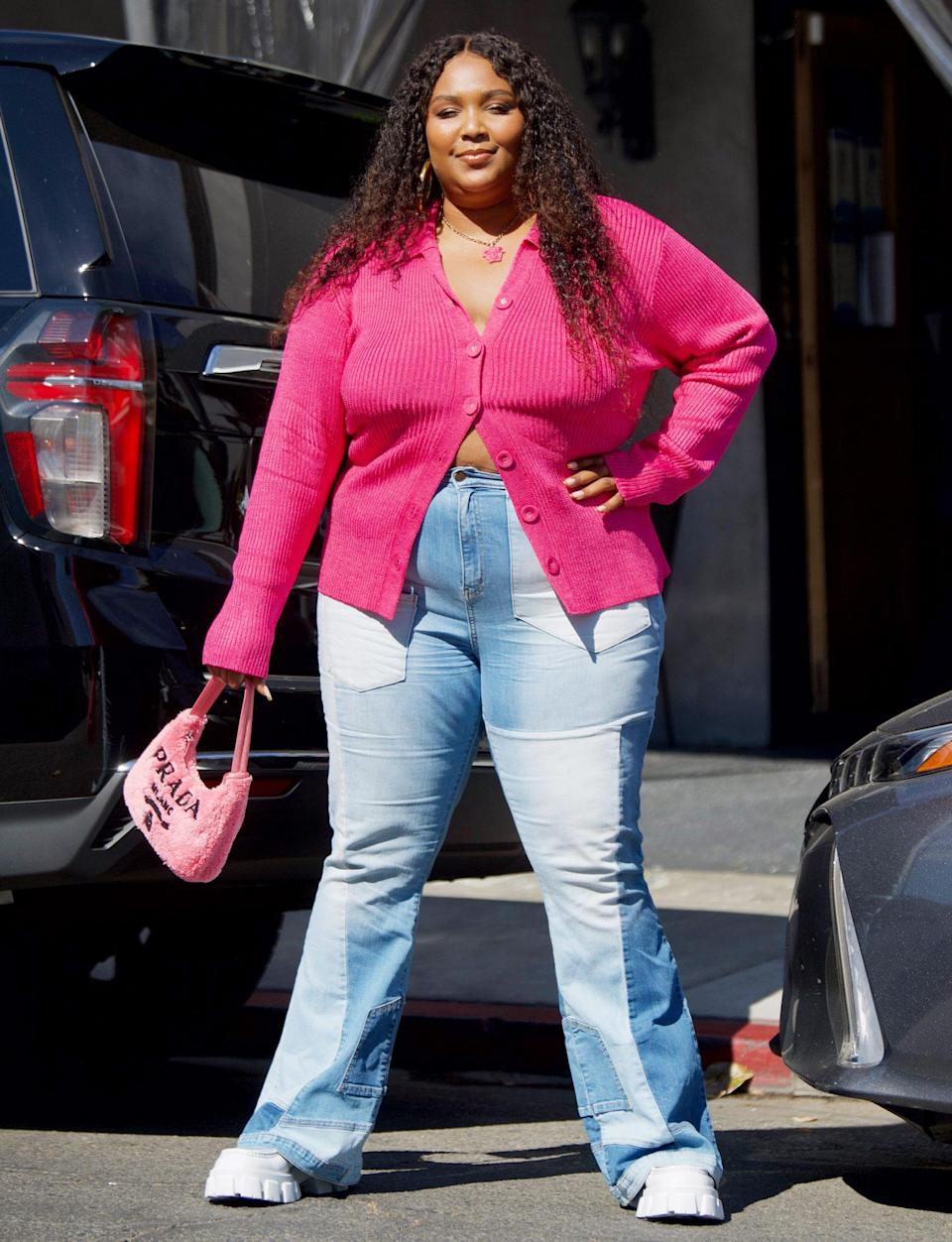 <p>Lizzo shows off her street style in a pink cardigan, pink Prada bag and patchwork denim on June 6 after grabbing lunch in L.A. </p>