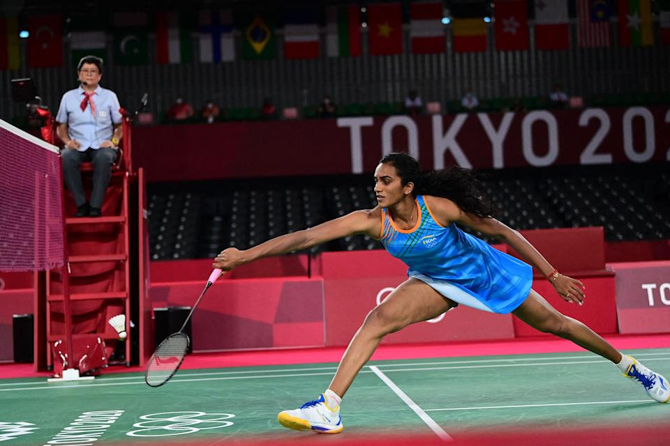 India's P. V. Sindhu hits a shot to China's He Bingjiao in their women's singles badminton bronze medal match during the Tokyo 2020 Olympic Games at the Musashino Forest Sports Plaza in Tokyo on August 1, 2021. (Photo by Pedro PARDO / AFP) (Photo by PEDRO PARDO/AFP via Getty Images)