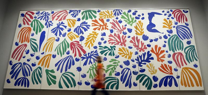 A woman a walks past 'The Parekeet and the Mermaid 1952' by Henri Matisse, on display during a media opportunity at The Tate Modern in London, Monday, April 14, 2014. The artwork is part of the 'Henri Matisse: The Cut-Outs' exhibition that runs at the gallery from April 17 until Sept. 7, 2014. (AP Photo/Kirsty Wigglesworth)