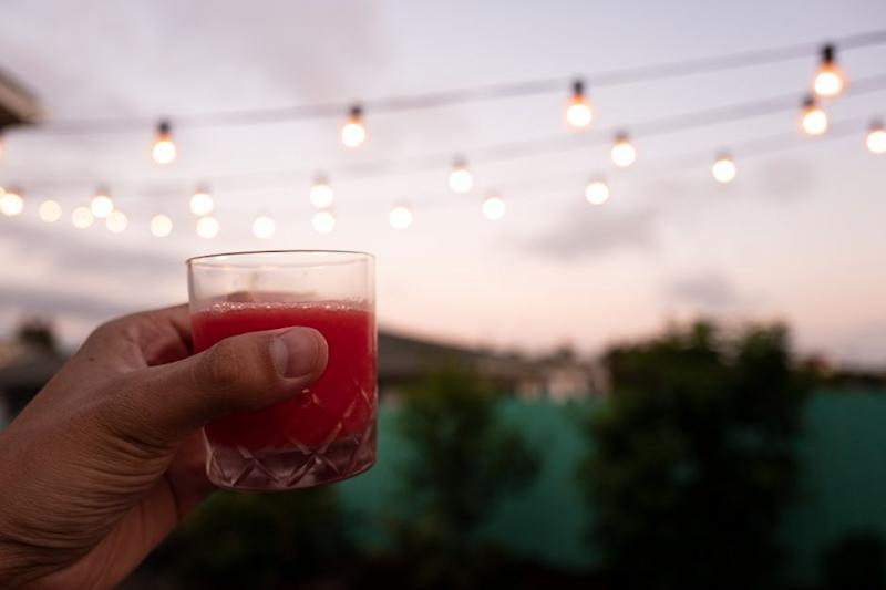 A photo of a hand holding up a glass of the finished cocktail: frosé. The scene is a backyard at sunset.