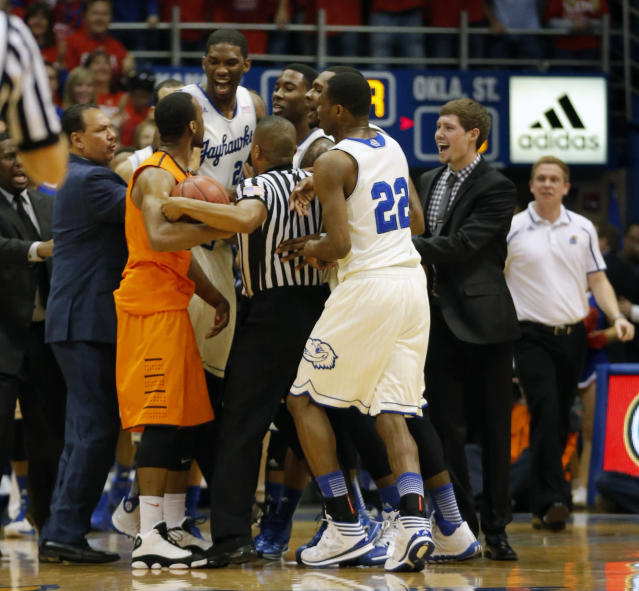 Referee Keith Kimble, center, gets between Oklahoma State guard Markel Brown (22) and Kansas center Joel Embiid (21), forward Jamari Traylor (31) and guard Andrew Wiggins (22) during the first half of an NCAA college basketball game at Allen Fieldhouse in Lawrence, Kan., Saturday, Jan. 18, 2014. (AP Photo/Orlin Wagner)