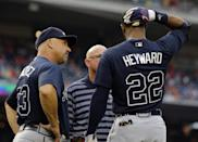 Atlanta Braves manager Fredi Gonzalez, left, and trainer Jeff Porter look over Atlanta Braves' Jason Heyward during the first inning of a baseball game against the Washington Nationals at Nationals Park Tuesday, Aug. 6, 2013, in Washington. Heyward continued his at bat, but left the game afterwards. (AP Photo/Alex Brandon)