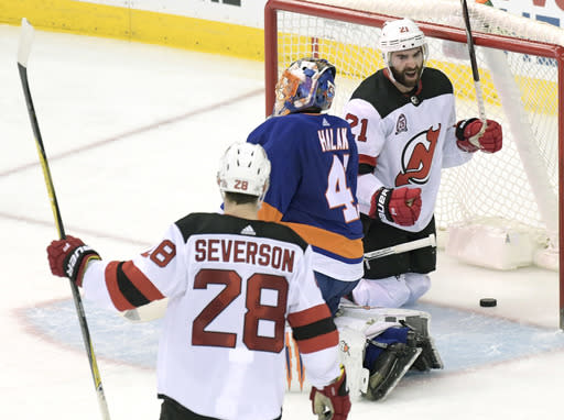 New Jersey Devils right wing Kyle Palmieri (21) celebrates his goal with New Jersey Devils defenseman Damon Severson (28) as New York Islanders goaltender Jaroslav Halak (41) reacts during the third period of an NHL hockey game Saturday, Feb. 24, 2018, in Newark, N.J. The Devils defeated the Islanders 2-1. (AP Photo/Bill Kostroun)