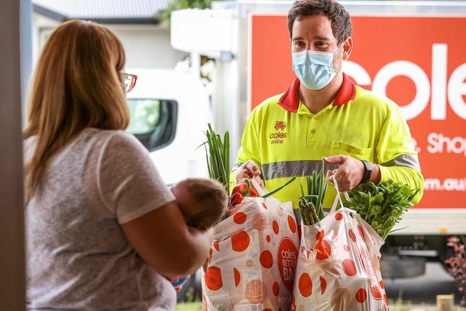 Coles delivery driver hands groceries to woman with baby. Source: Coles