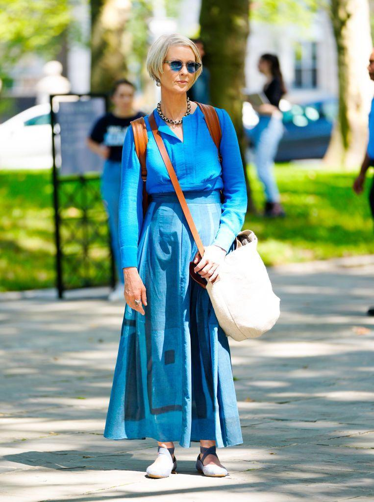 """<p>Miranda goes tonal! Wearing a blue linen shier and maxi skirt, Nixon's outfit was paired with <a href=""""https://www.amazon.co.uk/dp/B078H33NYZ/ref=twister_B00EC9LKE0"""" rel=""""nofollow noopener"""" target=""""_blank"""" data-ylk=""""slk:Jessica Simpson ballet pumps"""" class=""""link rapid-noclick-resp"""">Jessica Simpson ballet pumps</a> and a cross-shoulder bag by Australian brand Elk. </p>"""