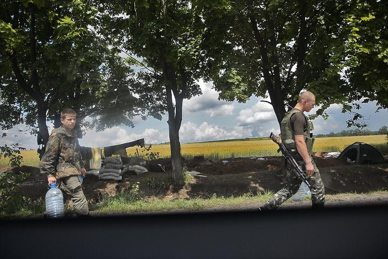Ukrainian soldiers carry supplies of water at a check point near the eastern city of Slavyansk, on June 11, 2014