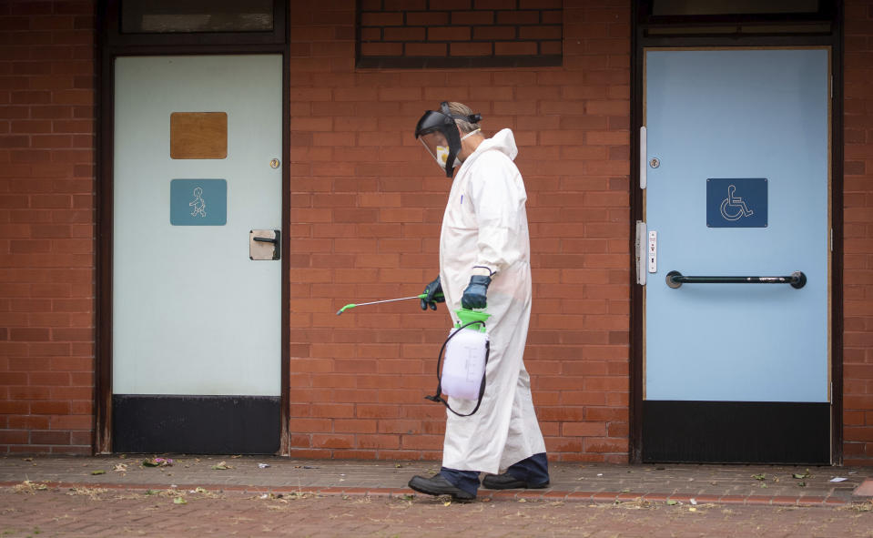 A worker for Leicester City Council disinfects public toilets in Leicester, England, Monday June 29, 2020. The central England city of Leicester is waiting to find out if lockdown restrictions will be extended as a result of a spike in coronavirus infections. (Joe Giddens/PA via AP)