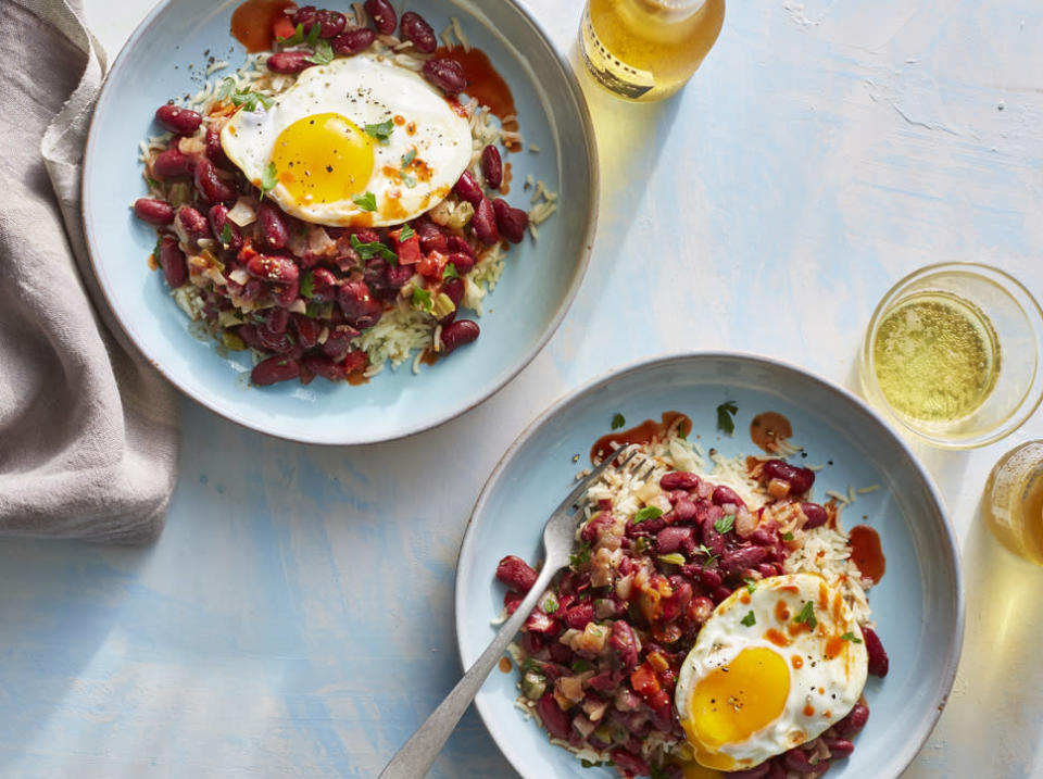 """<p>Red beans and rice is a tried and true standby for good reason—at its simplest, the dish is hearty and tasty, comes together fast, and can be whipped up with ease, even during those hectic weeks you can't seem to make it the grocery store. We amped up this largely <a href=""""https://www.myrecipes.com/ingredients/easy-meals-made-with-pantry-staples"""" rel=""""nofollow noopener"""" target=""""_blank"""" data-ylk=""""slk:pantry staple-based recipe"""" class=""""link rapid-noclick-resp"""">pantry staple-based recipe</a> with a runny-yolked fried egg and a package of frozen """"seasoning blend,"""" which includes chopped bell pepper, onion, and celery. If you have fresh onions, peppers, etc. on hand and a few extra minutes for chopping, feel free to go that route instead! Microwaveable rice keeps the dinner super speedy to prep, but you can use traditionally cooked rice here just as well. </p>"""