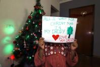 Daughter of Reuters cameraman Kumerra Gemechu poses with a note she prepared for her arrested father next to a Christmas tree in Addis Ababa