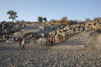 A Tigray refugees walk a hill after arriving on the banks of the Tekeze River on the Sudan-Ethiopia border, in Hamdayet, eastern Sudan, Wednesday, Dec. 2, 2020. Ethiopian forces on Thursday, Dec. 3, 2020 blocked people from the country's embattled Tigray region from crossing into Sudan at the busiest crossing point for refugees, Sudanese forces said. (AP Photo/Nariman El-Mofty)