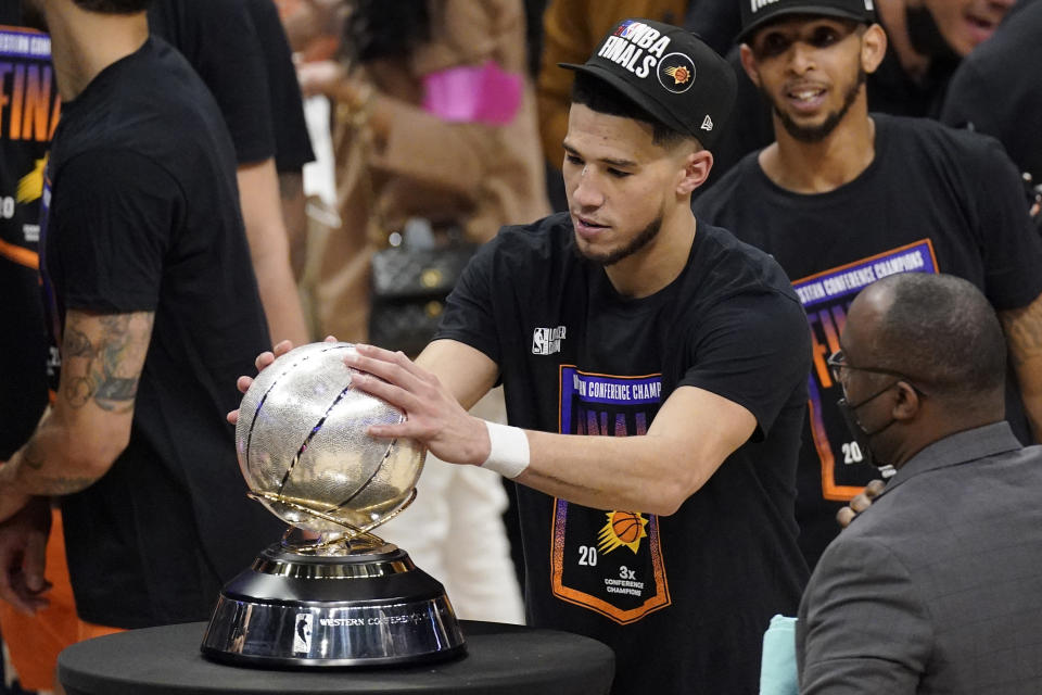 Phoenix Suns guard Devin Booker rubs the Western Conference trophy after they won Game 6 of the NBA basketball Western Conference Finals against the Los Angeles Clippers Wednesday, June 30, 2021, in Los Angeles. The Suns won the game 130-103 to take the series 4-2. (AP Photo/Mark J. Terrill)