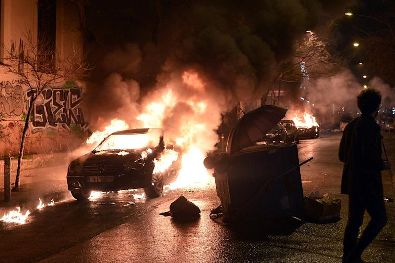 A man walks past a burning car in central Athens after it was set on fire by young anarchists at the end of a demonstration on February 26, 2015 (AFP Photo/Louisa Gouliamaki)